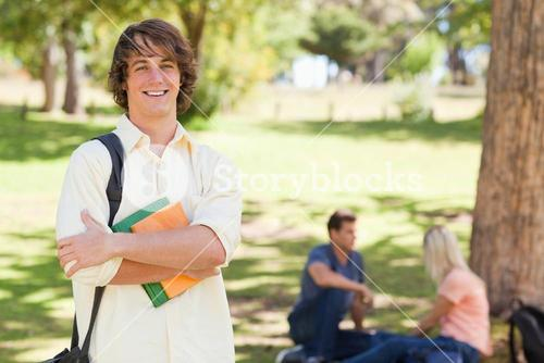 Young man posing with textbook