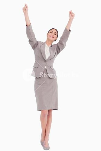 Young businesswoman with arms raised