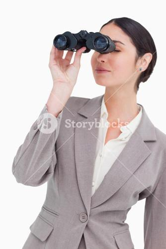 Businesswoman looking through spy glasses