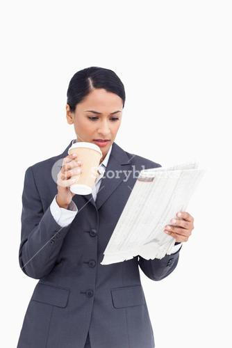 Close up of saleswoman with paper cup and newspaper