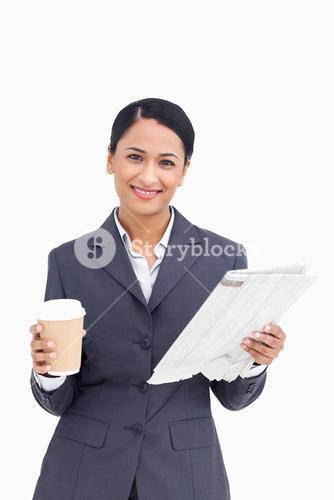 Close up of smiling saleswoman with paper cup and newspaper
