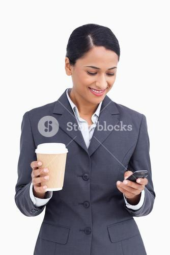 Close up of saleswoman with paper cup reading text message