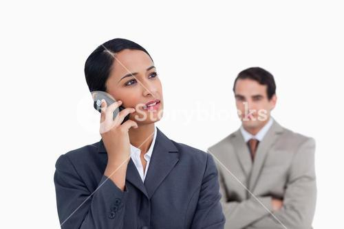 Saleswoman with colleague behind her listening closely to caller