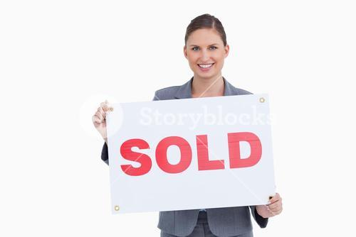 Smiling real estate agent presenting sold sign