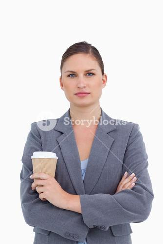 Tradeswoman with arms folded and paper cup