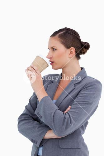 Side view of tradeswoman taking a sip out of her paper cup