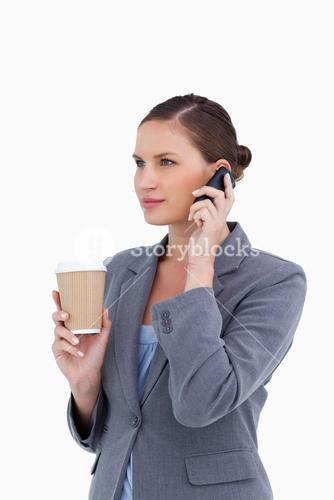 Tradeswoman with paper cup on her cellphone