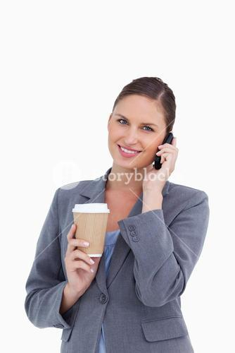 Smiling tradeswoman with paper cup on her cellphone