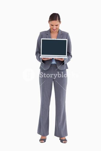 Tradeswoman presenting and looking at laptop screen