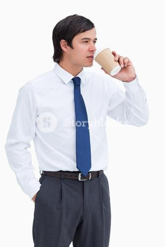 Tradesman drinking coffee out of a paper cup