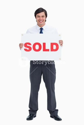 Smiling male real estate agent with sold sign