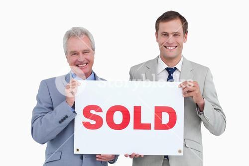 Smiling real estate agents holding sold sign