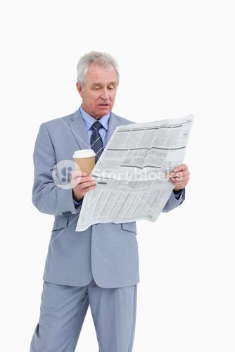 Mature tradesman with paper cup reading news paper