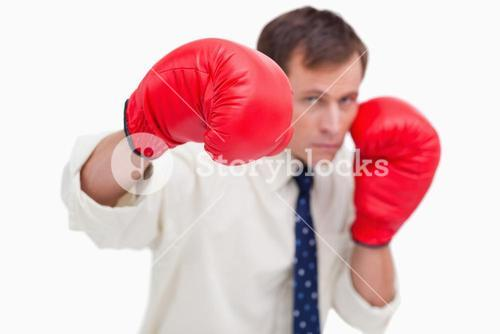 Punching businessman with boxing gloves