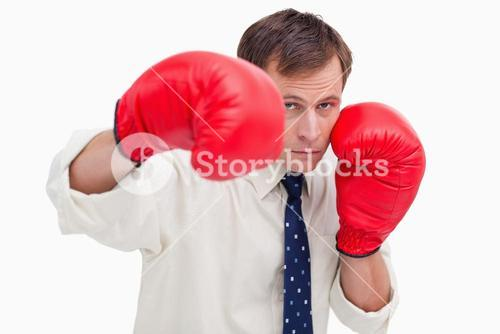 Striking businessman with boxing gloves