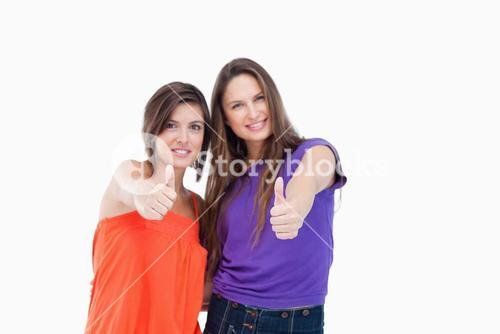 Two teenagers putting their thumbs up while smiling