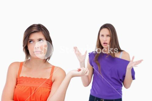 Exasperated teenager standing upright while her friend is roaring at her