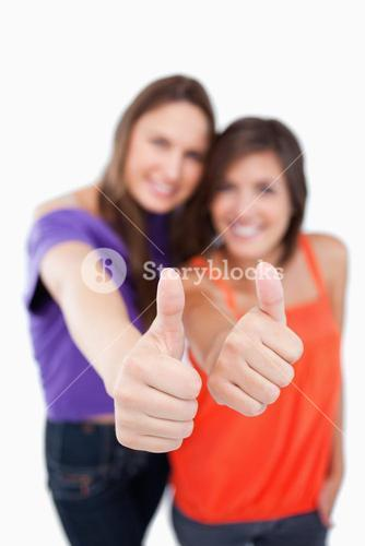 Two thumbs up being showed by teenagers