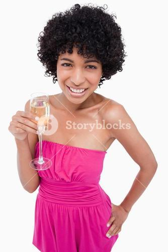 Young woman holding a glass of champagne with her hand on her hip