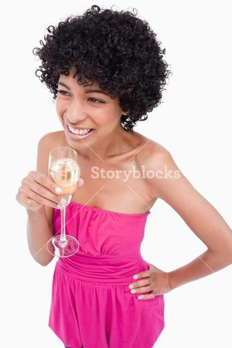 Young female looking to the side with a hand on her hip and drinking champagne