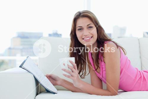 Young woman showing a great smile while reading and drinking coffee