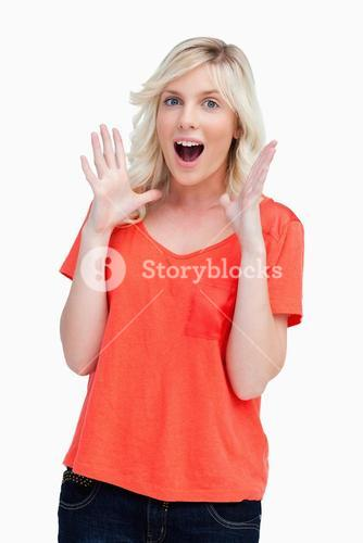 Surprised teenager standing upright with her arms next to her head