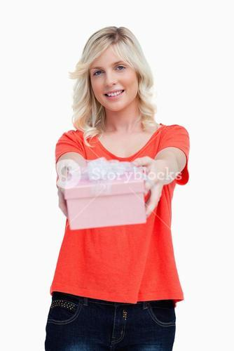 Happy young woman holding her birthday gift in front of her