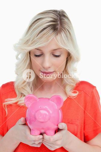 Young woman looking at a piggy bank held by her hands