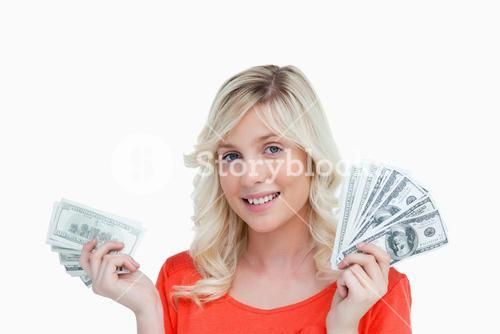 Woman showing a great smile while holding two fans of dollar notes