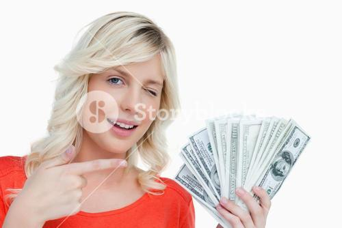Woman winking an eye while pointing her finger on dollar notes