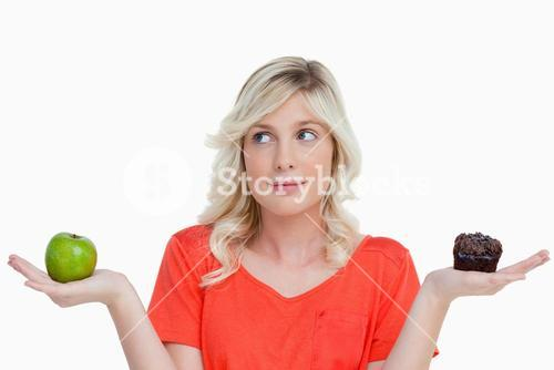 Woman hesitating between a chocolate muffin and a green apple
