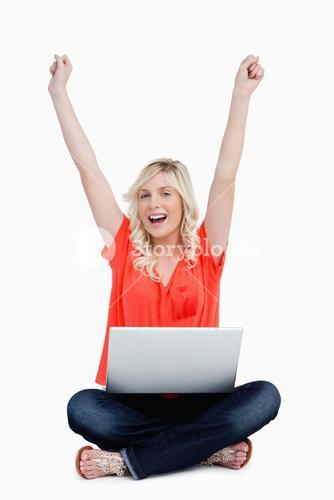 Attractive woman sitting crosslegged while raising her arms above the head