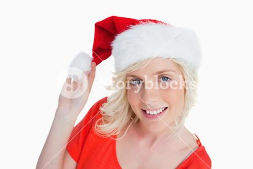 Young woman holding the pompom of her Christmas hat