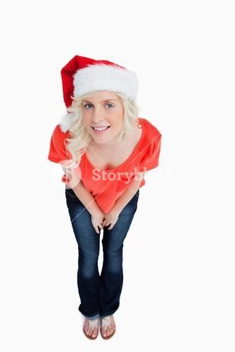 Fairhaired woman wearing the Santa Claus hat while leaning forward