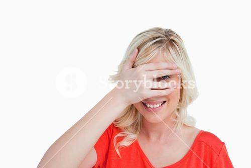 Young woman trying to see through her fingers placed in front of her face