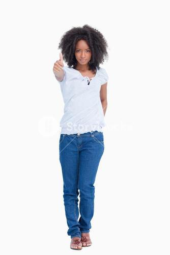 Serious woman standing upright with her thumbs up and a hand on her back