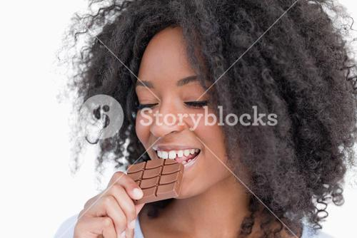 Young woman eating a delicious piece of chocolate bar