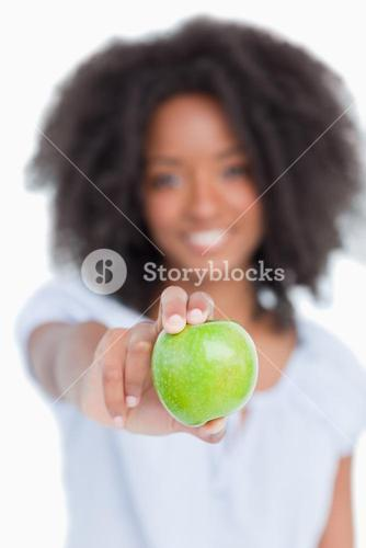 Green apple held by a young woman with curly hair