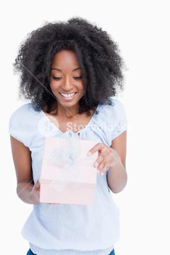 Happy young woman opening her birthday gift