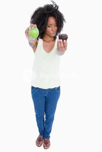 Young woman holding a muffin and a green apple and hesitating
