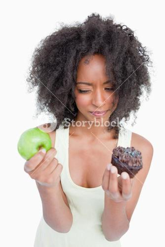 Young woman hesitating between a chocolate muffin and a green apple