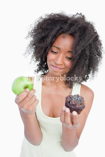 Young woman hardly hesitating between a muffin and an apple
