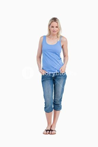 Relaxed blonde woman standing upright with hands in pockets