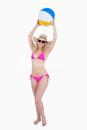Smiling teenager in a pink swimsuit raising a beach ball above her head
