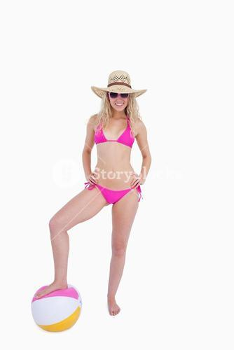 Smiling teenager putting her hands on her hips while placing a foot on a beach ball
