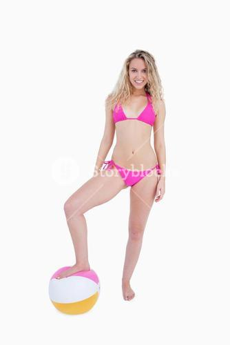 Smiling attractive teenager placing her foot on a beach ball