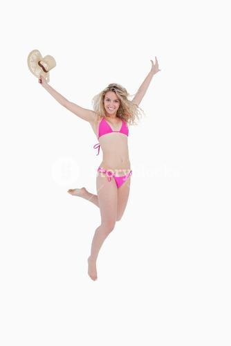 Smiling young woman raising her arms while flicking her leg back