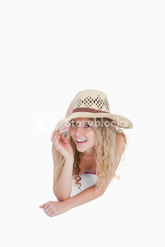 Smiling teenager lying down while holding her hat brim
