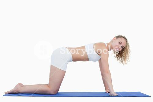 Side view of a young attractive woman doing gymnastics on all fours