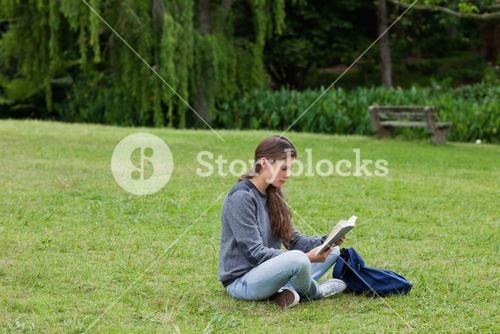Young girl sitting with her legs crossed while reading a book
